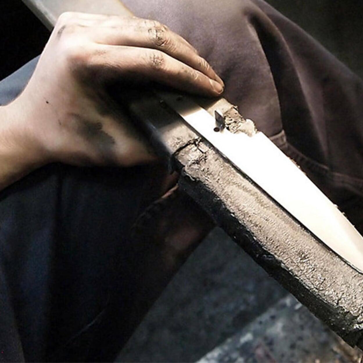 sharpening a kitchen knife on sharpening steel